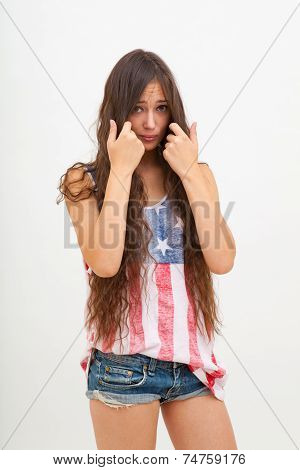 Beautiful woman in top colors of USA flag, jeans. Touching her long hair