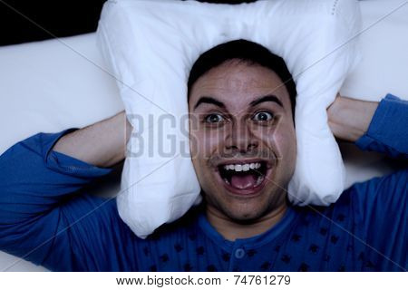 Insomniac man using a pillow to cover his ears