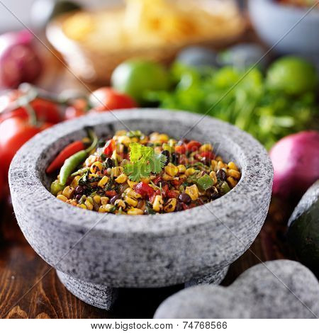 fire roasted corn and black bean salsa in stone molcajete