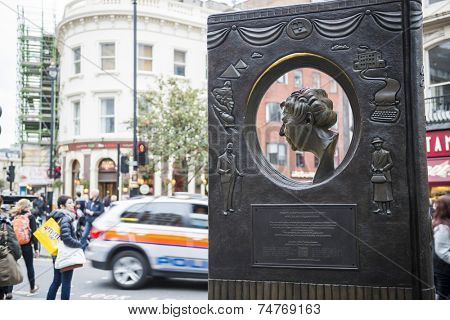 LONDON, UK - OCTOBER 26: Agatha Christie book shaped memorial with busy street in the background. The bronze memorial was unveiled on the 18 November 2012. October 26, 2014 in London.