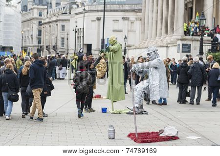 LONDON, UK - OCTOBER 26: Street artists levitating in busy Trafalgar Square. In central London, street artists must obtain a permit in order to perform in public spaces. October 26, 2014 in London.