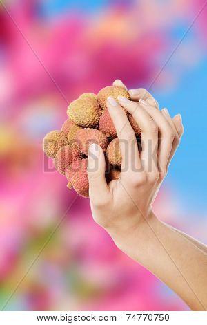 Beautiful nude woman holding litchi