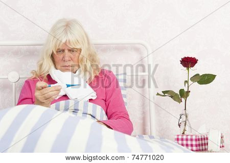 Woman Sitting In Bed Lloking At Thermometer