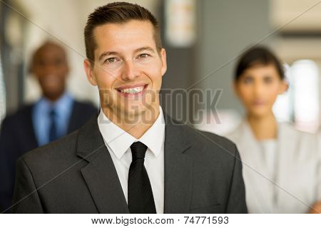 good looking young business man with colleagues on background