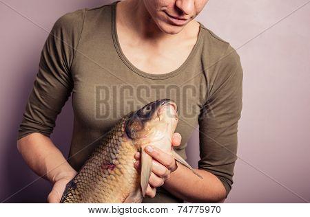 Young Woman Examinig A Carp