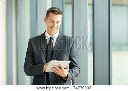good looking young entrepreneur using tablet computer in office