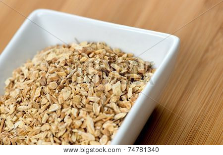 Macro Of Astragalus Root Chips Against A Wooden Board
