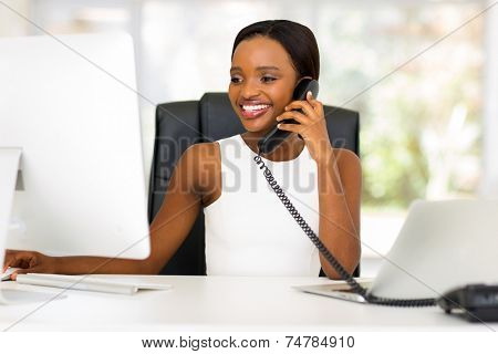 happy african businesswoman talking on landline phone and looking at computer