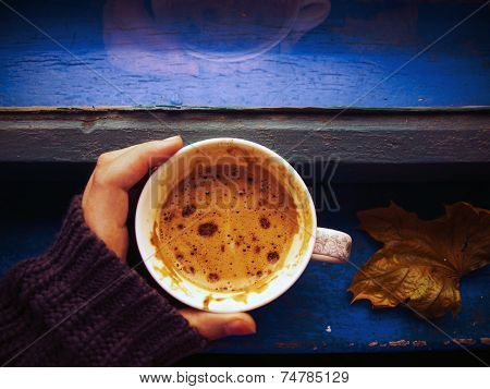 Hand in winter sweater holding a cup of coffee