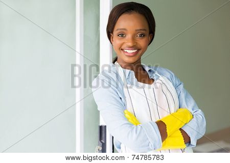 portrait of young african woman wearing apron at home