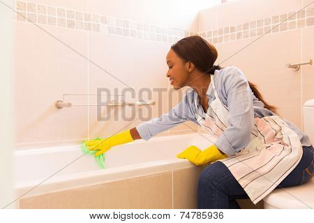 young african housewife cleaning up bathtub at home