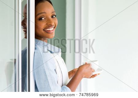 beautiful young african woman drinking tea at home after house chores