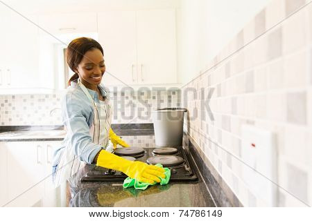 smiling african woman cleaning the stove
