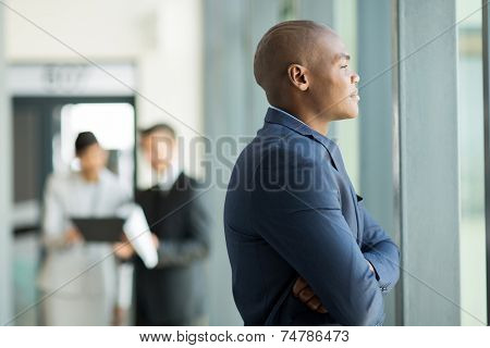 thoughtful african american businessman inside an office building looking outside the window