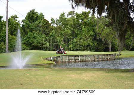 Man Mowing a Golf Course Green