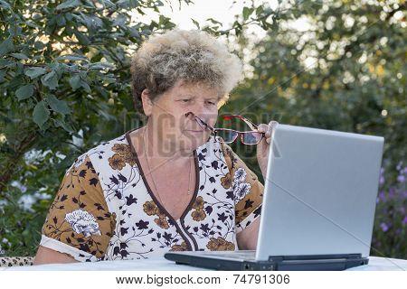 elderly woman working on  computer in the garden