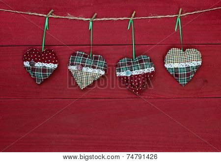 Christmas hearts hanging on clothesline by antique red country wooden background