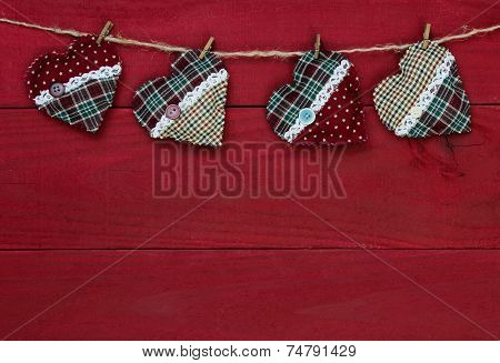 Plaid country Christmas hearts hanging on clothesline by antique red wood background