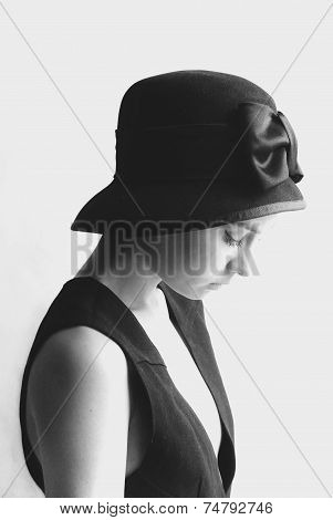 portrait photo of the girl in the black hat and little black dress.black and white photo
