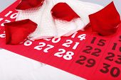 foto of menses  - Sanitary pads and rose petals on wooden table on calendar background - JPG