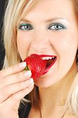 Beautiful Blond Girl Eating A Strawberry