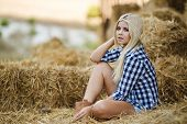 picture of cowgirls  - Beautiful blonde cowgirl posing for a photograph while sitting on hay on a hot summer day in the countryside - JPG