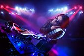 stock photo of disc jockey  - Handsome disc jockey playing music with light beam effects on stage - JPG