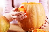 foto of hollow  - Hollowing out pumpkin to prepare halloween lantern - JPG