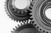 picture of interlocking  - Closeup of three metal cog gears - JPG
