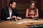 stock photo of competing  - Handsome  man and beautiful woman in casino competing  holding in hands chips and cards sitting at table - JPG