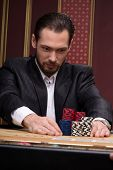 picture of shiting  - Handsome  confident man   in casino staking  up red blue and shite chips in piles   looking at  chips   sitting at table with  chips and cards waist up selective focus - JPG