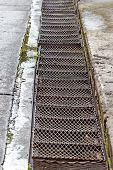 stock photo of gutter  - Drain Gutter In The Road, Next To Pavement, Showing Curb