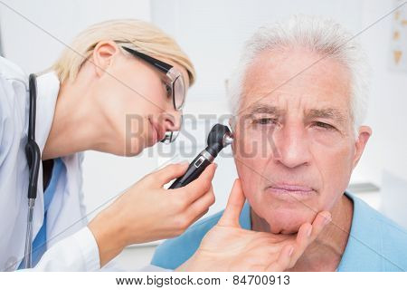 Female doctor examining senior patients ear with otoscope in clinic