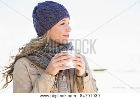 Thoughtful blonde in warm clothes holding hot beverage in the city