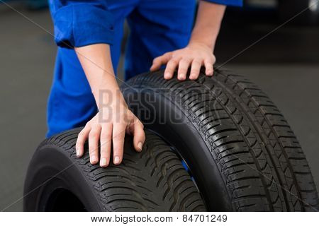 Mechanic rolling a tire wheel at the repair garage