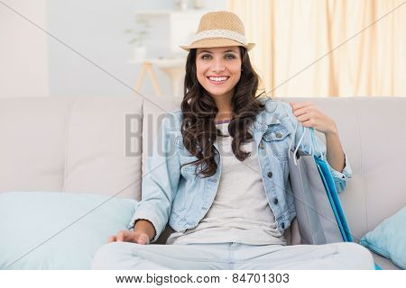 Pretty brunette looking at shopping bags at home in the living room