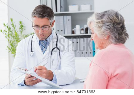 Male doctor explaining prescriptions to senior woman in clinic