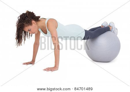 Fit woman wokring out on exercise ball on white background