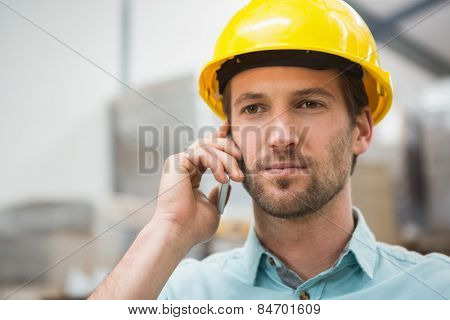Worker in hard hat using mobile phone in the warehouse