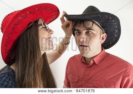 Young Couple With Cowboy Hats And Glasses Making Silly Faces On White Background