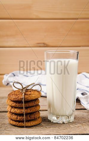 rustic oatmeal cookies on wooden table with a glass of milk