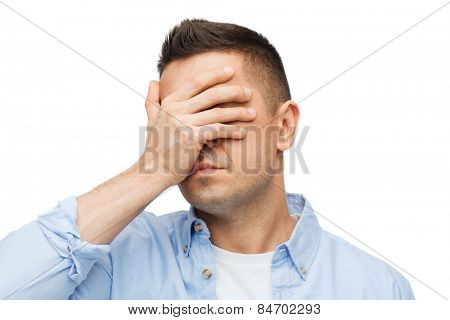 stress, headache, health care and people concept - unhappy man covering his eyes by hand