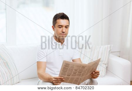 leisure, information, people and mass media concept - man reading newspaper at home