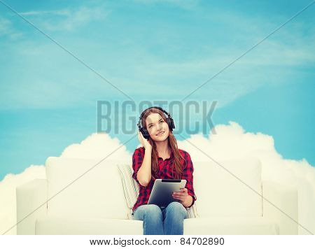 home, leisure, technology and happiness concept - smiling teenage girl sitting on sofa with headphones and tablet pc computer