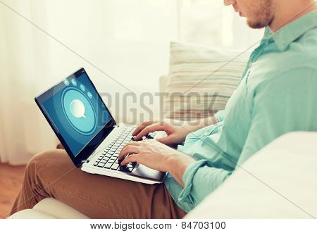 technology, leisure, advertisement and lifestyle concept - close up of man working with laptop computer displaying text bubble icon on screen and sitting on sofa at home