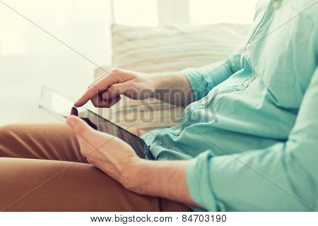 technology, leisure, lifestyle and distance learning concept - close up of man working with tablet pc computer sitting on sofa at home
