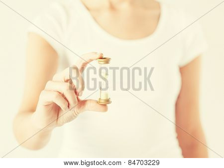 close up of woman hand holding hourglass.