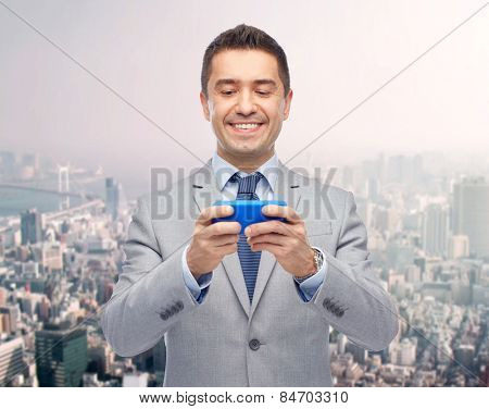 business, people and technology concept -happy businessman texting or playing game on smartphone over city background