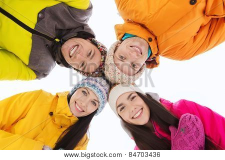 winter, leisure, friendship and people concept - happy friends standing in circle outdoors and looking down
