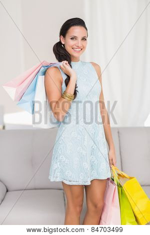 Stylish brunette with shopping bags at home in the living room